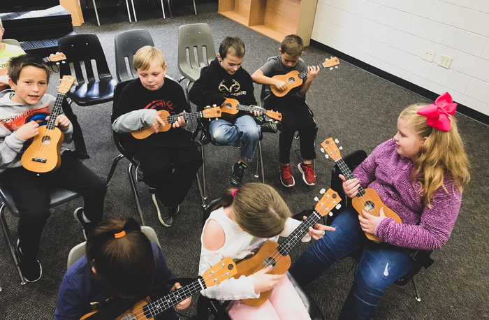 3rd Grade students working hard to figure out their ukulele finger positions.